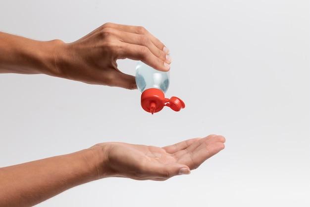 Osoba używająca butelki środka odkażającego do rąk