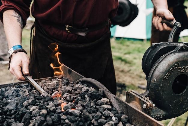 Osoba używająca rozżarzonego węgla z wyposażeniem kowalskim
