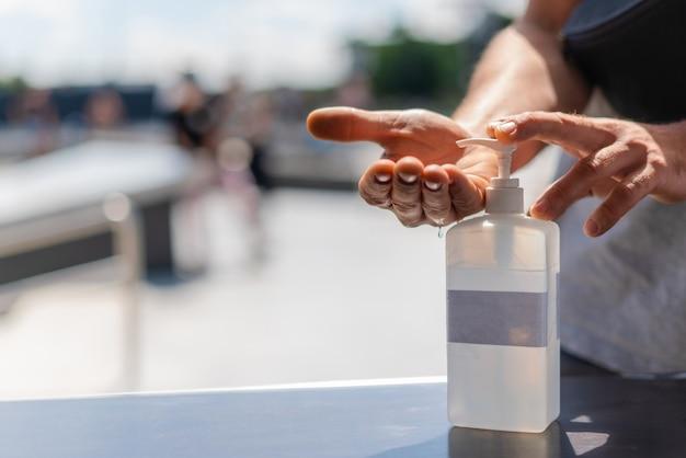Osoba używająca żelu do dezynfekcji rąk w miejscach publicznych. ręcznie wyciskana butelka z balsamem antybakteryjnym na zewnątrz.