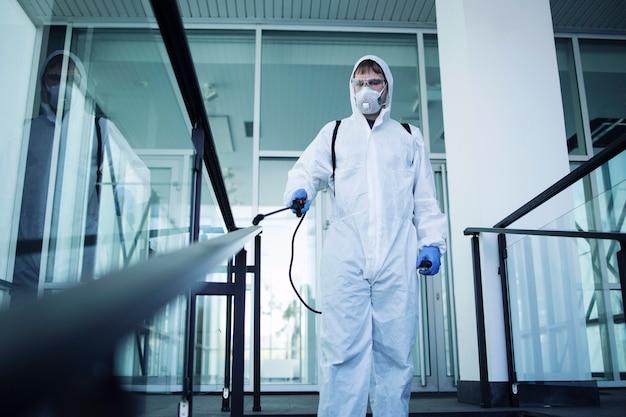 Osoba w białym kombinezonie chroniącym przed chemikaliami, dezynfekuje miejsca publiczne, aby powstrzymać rozprzestrzenianie wysoce zaraźliwego wirusa koronowego
