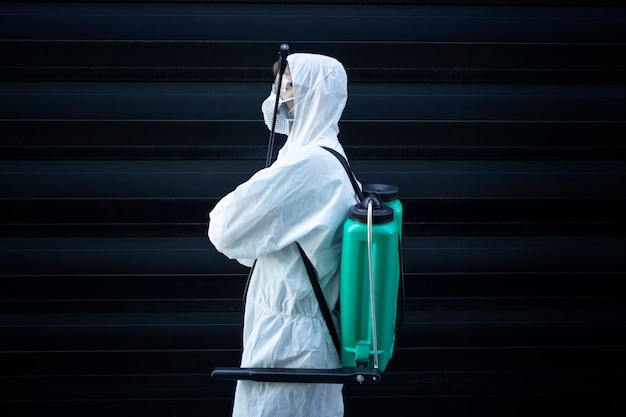 Osoba w białym kombinezonie chroniącym przed chemikaliami trzymająca rozpylacz ze środkami dezynfekującymi w celu powstrzymania rozprzestrzeniania wysoce zaraźliwego wirusa