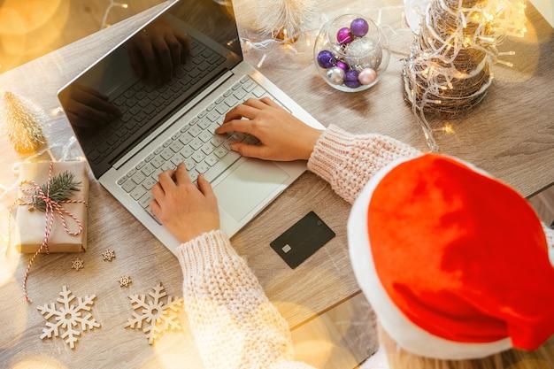 Osoba w czapce mikołaja kupująca online prezenty i ozdoby świąteczne przy laptopie z bożonarodzeniowymi światłami bokeh