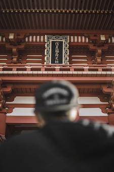Osoba w czarnej czapce przed wieżą