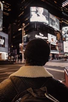 Osoba w czarnej dzianinowej czapce i brązowej kurtce, stojąca nocą na ulicy