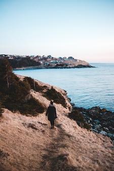 Osoba w czarnej kurtce stojąca na formacji skalnej w pobliżu zbiornika wodnego w ciągu dnia