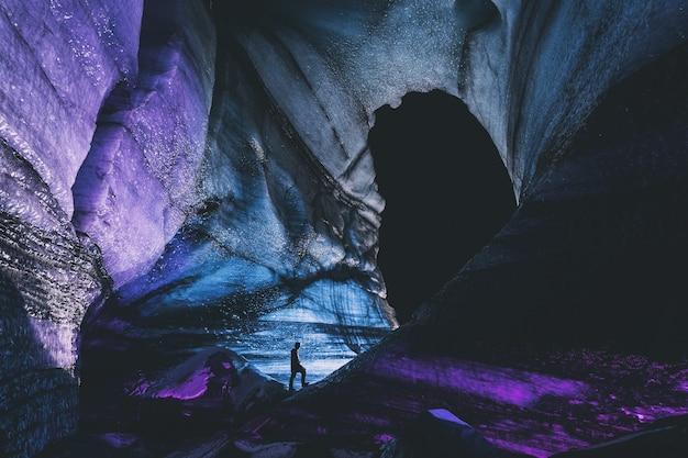 Osoba w czarnej kurtce stojąca na formacji skalnej