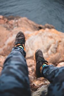 Osoba w czarnych spodniach i brązowych butach turystycznych siedzi na skale w ciągu dnia