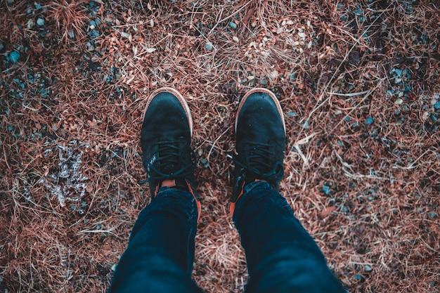Osoba w czarnych spodniach i czarnych butach stojących na brązowych suszonych liściach