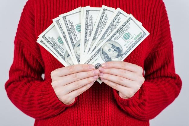 Osoba w czerwonym swetrze trzyma wachlarza dolarów