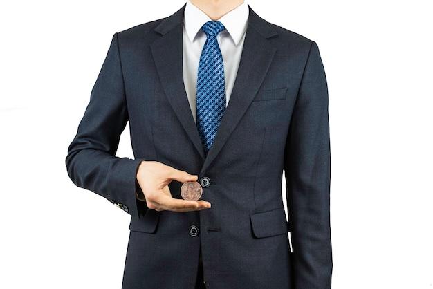 Osoba w garniturze i trzymająca w dłoni bitcoina.