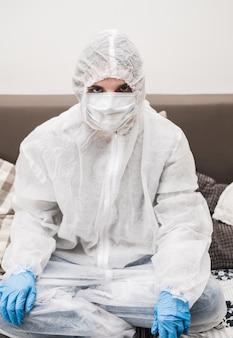 Osoba w kombinezonie ochronnym, niebieskie gumowe rękawice, maska medyczna