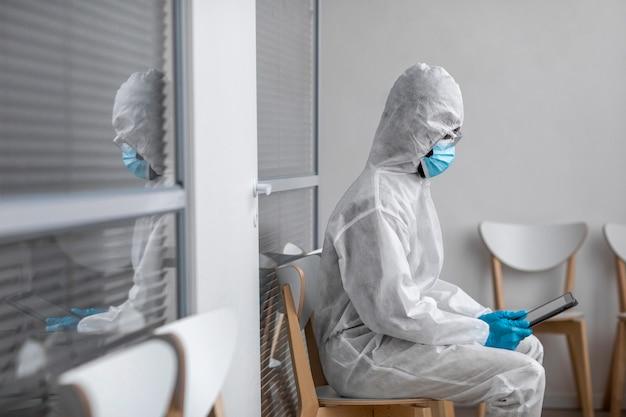 Osoba w kombinezonie ochronnym patrząc na tablet