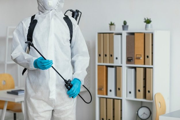 Osoba w kombinezonie ochronnym przygotowuje się do dezynfekcji pomieszczenia