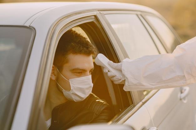 Osoba w kombinezonie ochronnym sprawdza temperaturę