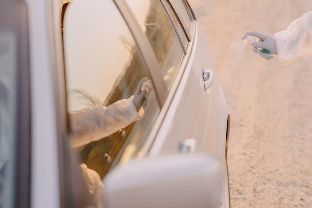 Osoba w kombinezonie ochronnym zdezynfekuje samochód