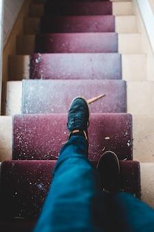 Osoba w niebieskich dżinsach i czarnych butach