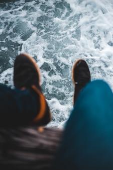 Osoba w niebieskie spodnie i brązowe buty stojące na brązowy drewniany dok