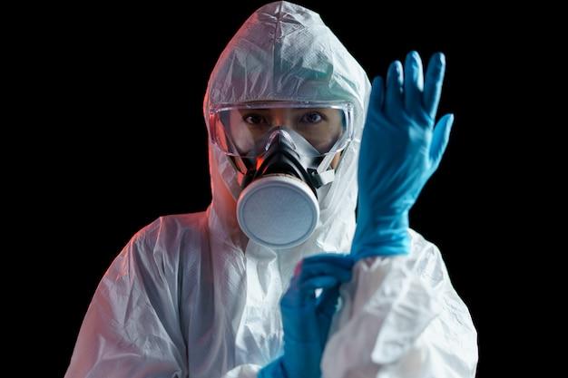 Osoba w stroju ochronnym w gumowych rękawiczkach na ciemnej ścianie