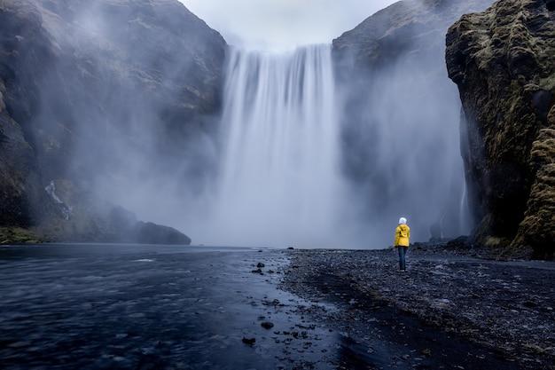 Osoba w żółtej kurtce stojąca przy hipnotyzującym wodospadzie