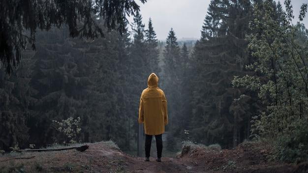 Osoba w żółtym płaszczu przeciwdeszczowym w ponurym lesie na wzgórzu w deszczu