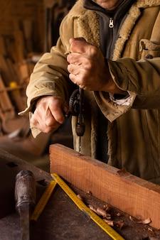 Osoba wiercąca otwory w drewnie