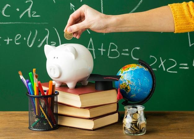 Osoba wkładająca monety do skarbonki z książkami i ołówkami