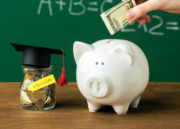 Osoba wkładająca pieniądze do skarbonki ze słoikiem i czapką akademicką