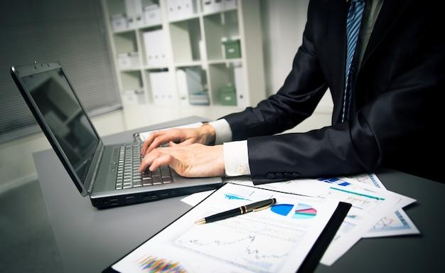 Osoba wpisująca na nowoczesny laptop w biurze