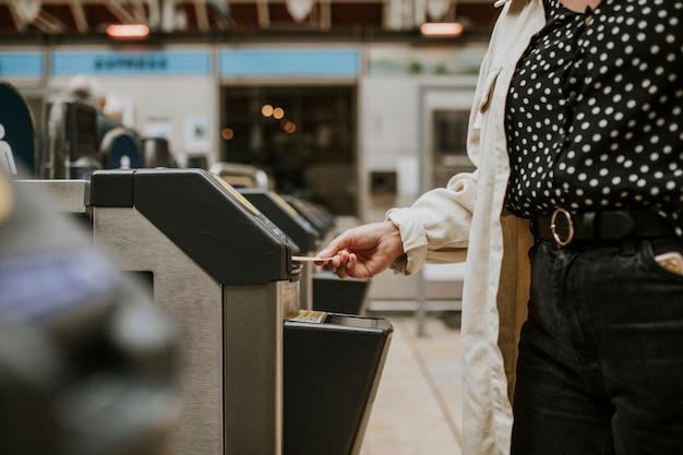 Osoba wstawiająca bilet do kołowrotu na stacji kolejowej