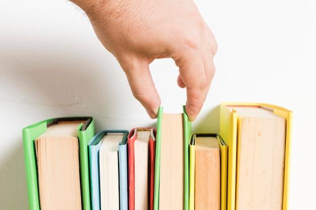 Osoba wybiera książkę z półki