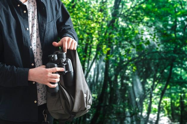 Osoba wyjmująca lornetkę z torby i regulująca ją