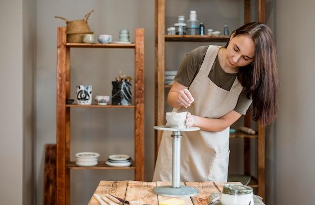 Osoba wykonująca gliniany garnek w swoim warsztacie