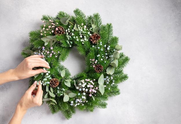 Osoba wykonująca wieniec świąteczny z kwiatami eukaliptusa i szyszkami prezent świąteczny własnoręcznie zrobiony