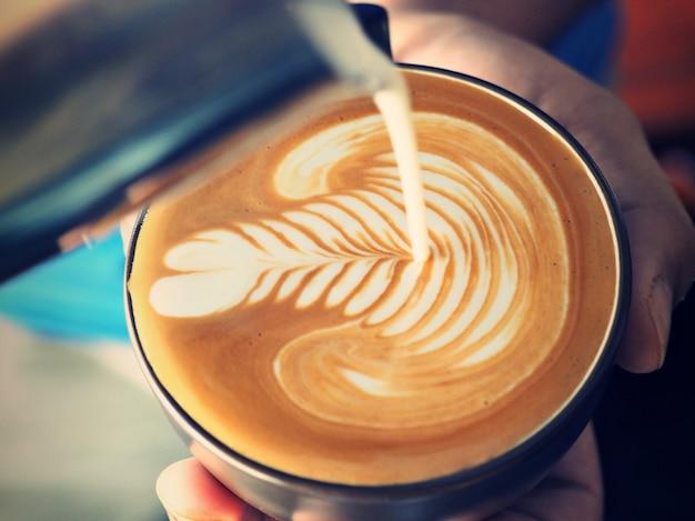 Osoba wylewanie mleka do filiżanki kawy