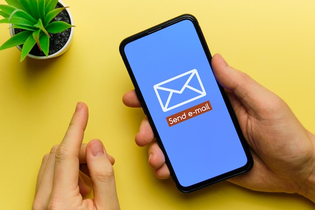 Osoba wysyła wiadomość e-mail za pomocą smartfona w rękach.