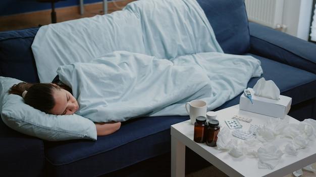 Osoba z chorobą śpi owinięta kocem na kanapie