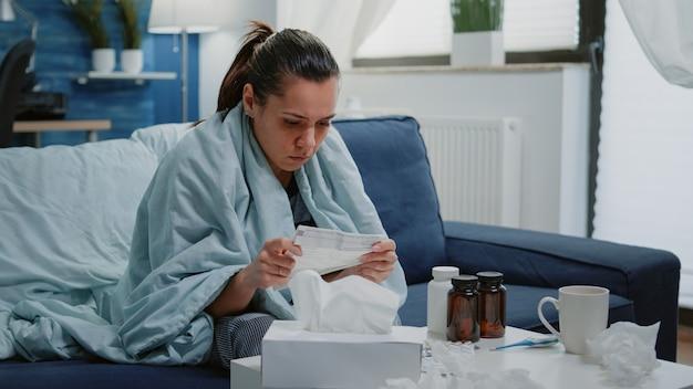 Osoba z infekcją chorobową analizująca ulotkę dołączoną do opakowania
