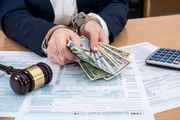 Osoba z kajdankami trzyma pieniądze