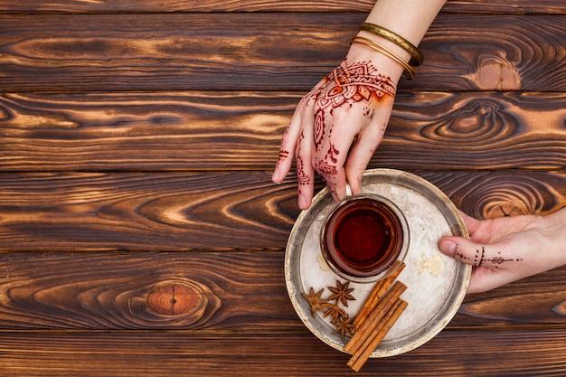 Osoba z mehndi trzyma herbacianą filiżankę na dużym talerzu