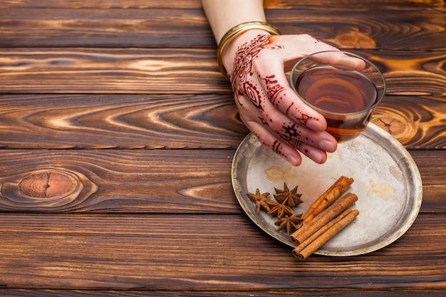 Osoba z mehndi trzyma herbacianą filiżankę na stole