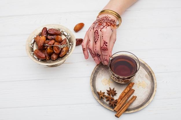 Osoba z mehndi trzyma herbacianą filiżankę na talerzu