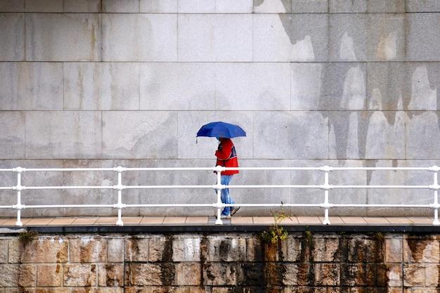 Osoba z parasolem w deszczowe dni w sezonie zimowym