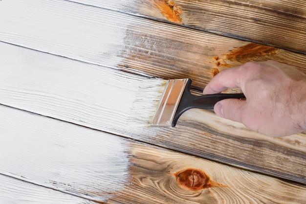 Osoba z pędzlem w rękach maluje białą farbą drewniane powierzchnie