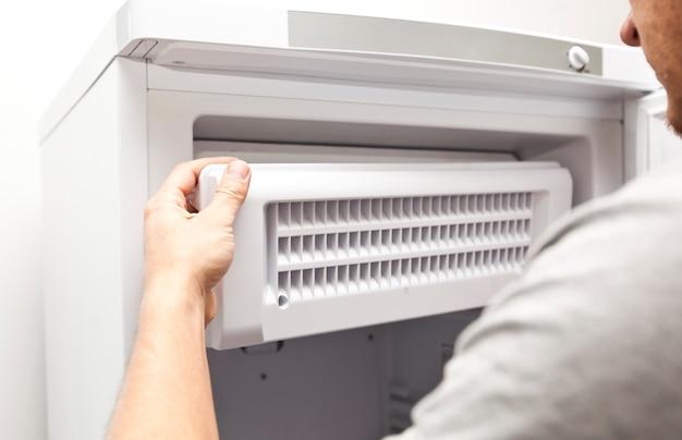Osoba zajmująca się naprawami naprawia zamrażarkę w domu