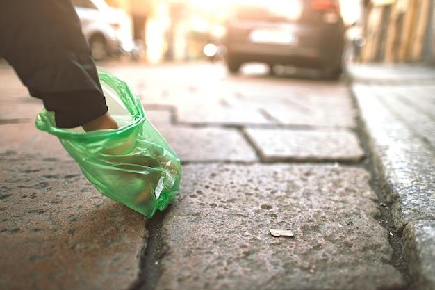 Osoba zbiera z torbą odchodów psa w mieście