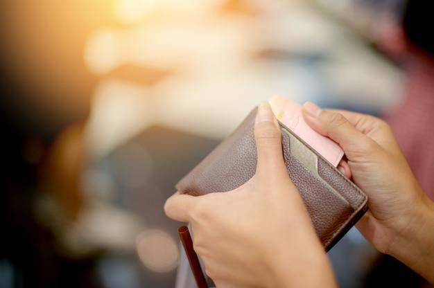 Osoba zbierająca pieniądze z portfela