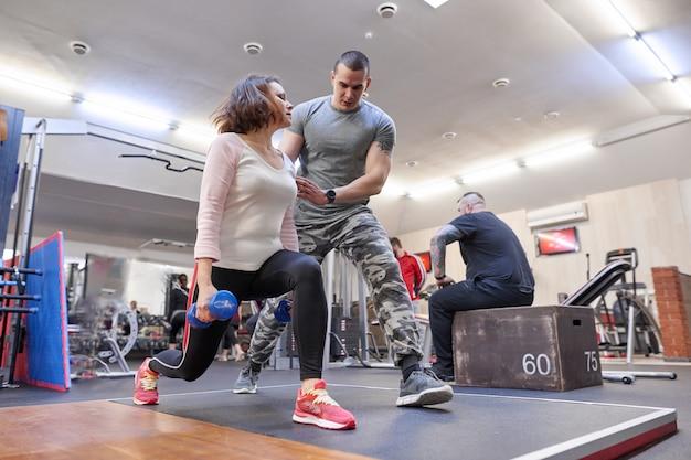 Osobisty instruktor fitness pomaga letniej kobiecie ćwiczyć