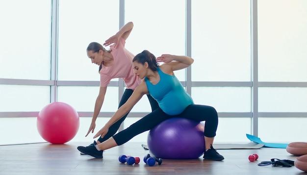 Osobisty trener fitness pomaga w ćwiczeniach dla kobiet w ciąży