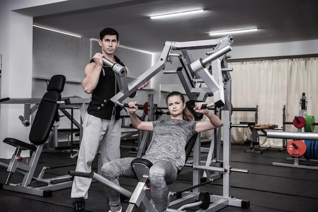 Osobisty trener instruujący młodą kobietę w siłowni