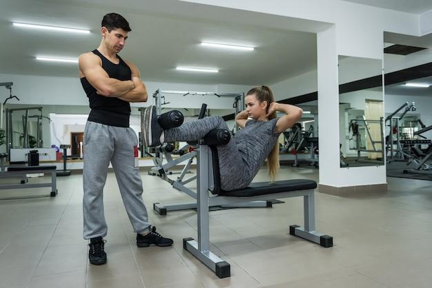 Osobisty trener patrząc na kobietę robi ćwiczenia
